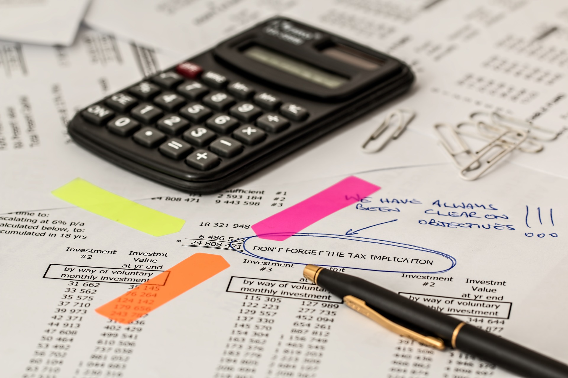 Papers with a calculator and pen. Click here to go to the accounting page.