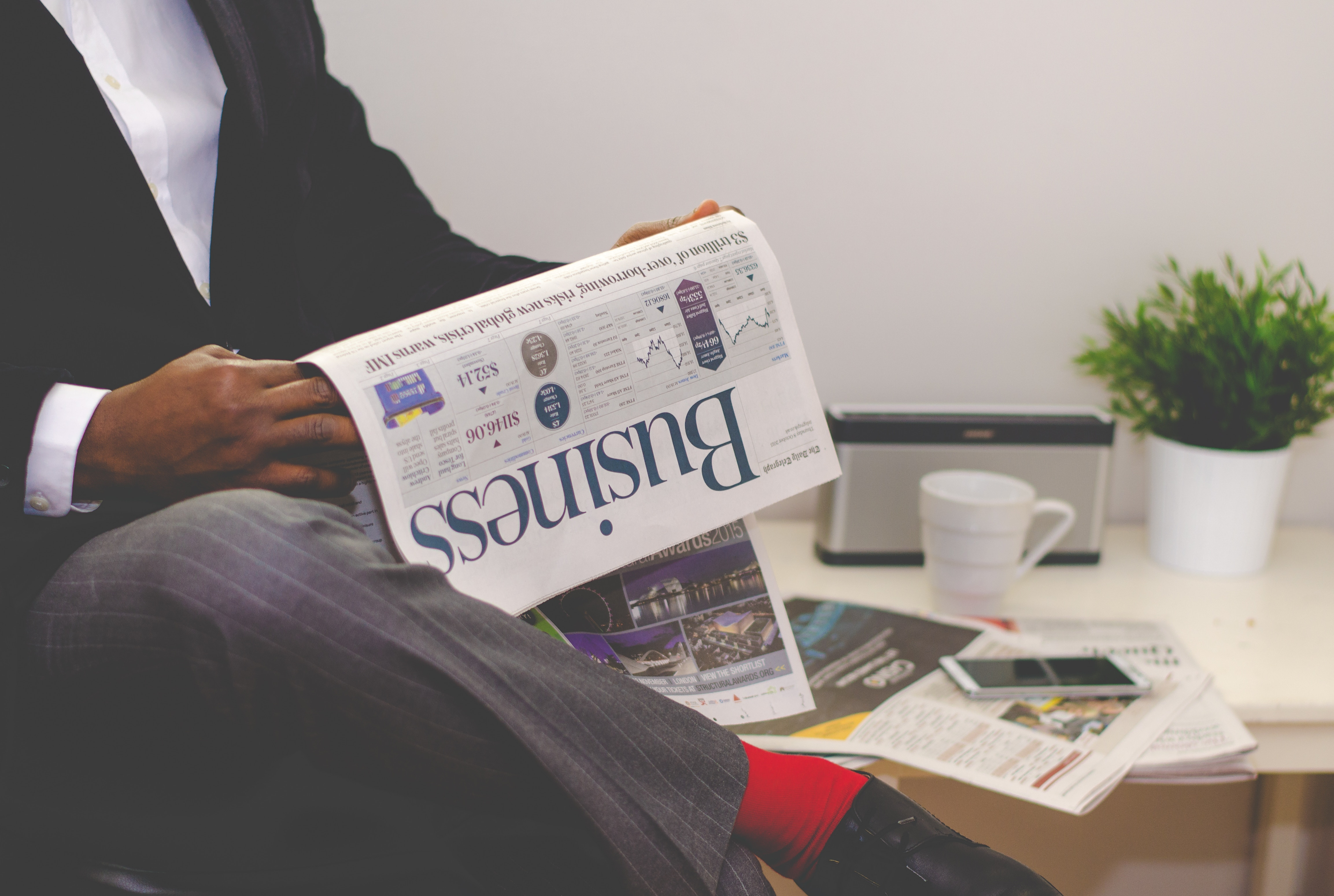 A man reading a newspaper. Click here to go to the Economics and Finance Department.