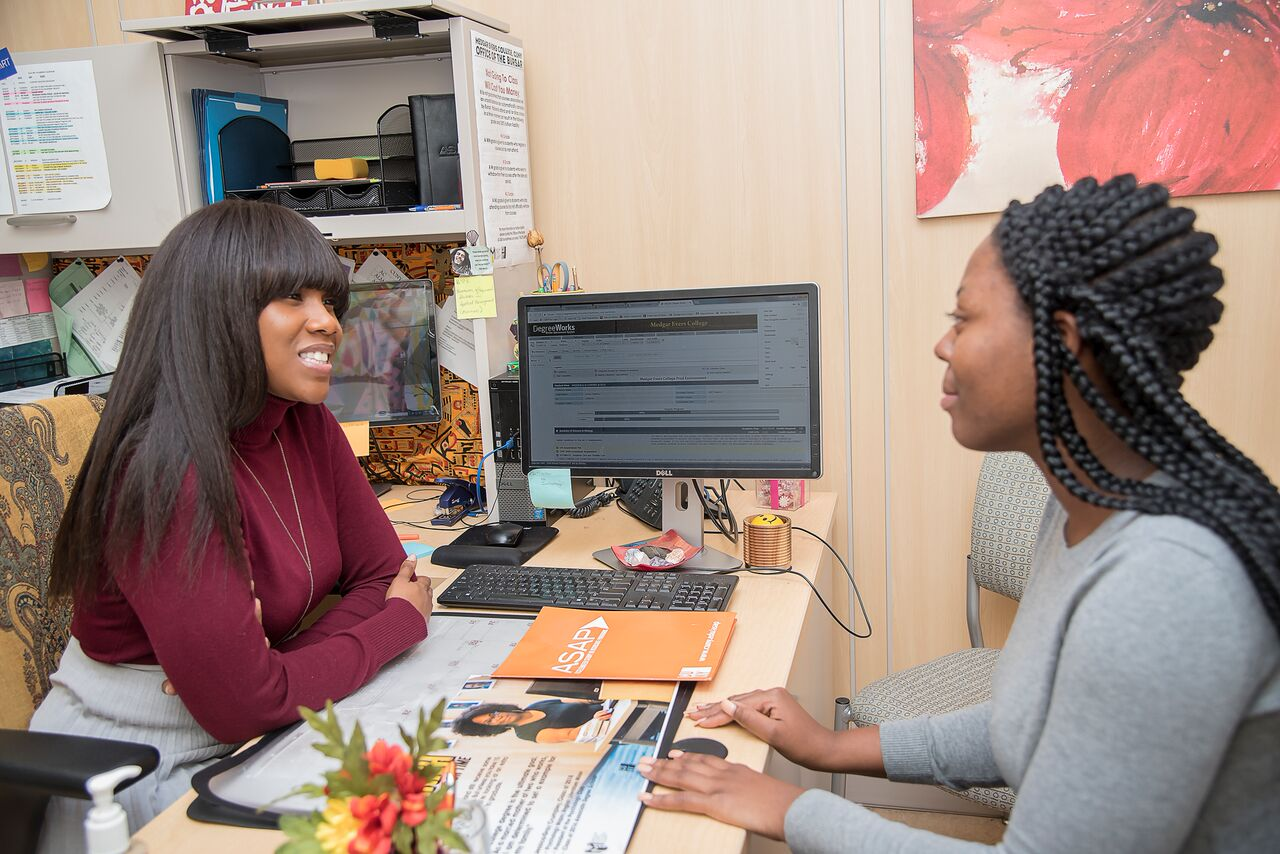 Advisor assisting student in office