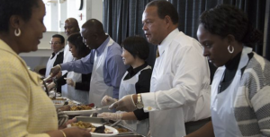 Dr. Crew serving food at community event